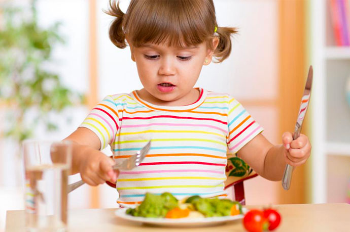 A child with knife and fork in hand about to eat a plate of vegetables